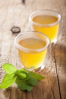 Ziołowa herbata szałwiowa z zielonymi liśćmi w szklanych kubkach