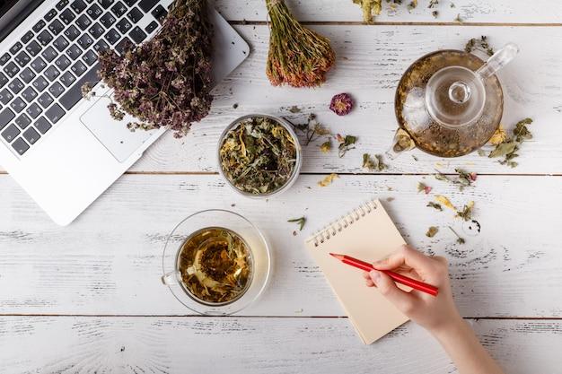 Ziołowa herbata w drewnianej łyżki zakończeniu up na stole. leżał płasko