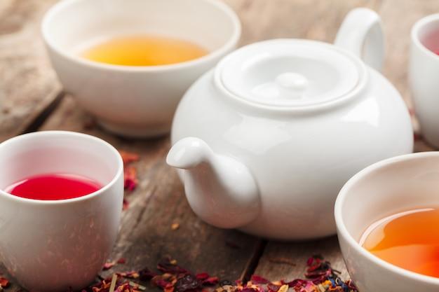 Ziołowa herbata w filiżankach na drewnianym tle