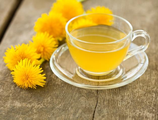 Ziołowa herbata z mniszka lekarskiego w szklanej filiżance na stole