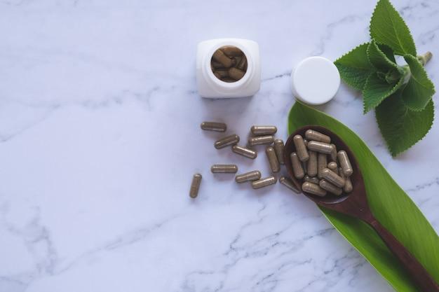 Ziołowa kapsułka z ziołowej natury na białym marmurze z liśćmi ziół i przestrzenią do kopiowania, medycyną i koncepcją leków