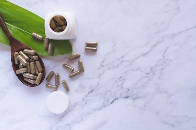 Ziołowa medycyna w kapsułach na drewnianej łyżce z naturalnym zielonym liściem na białym marmurze