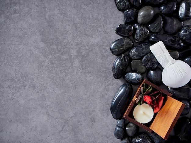 Ziołowa piłka kompresyjna umieszczona na czarnym kamieniu.