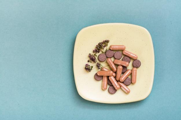 Ziołowe kapsułki lecznicze, tabletki i suszone oregano na spodku na zielonym stole. medycyna alternatywna. skopiuj miejsce