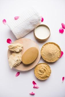 Ziołowe lub ajurwedyjskie opakowanie do twarzy z multani mitti, mlekiem itp. umieszczone na mydle, ręczniku. selektywne skupienie