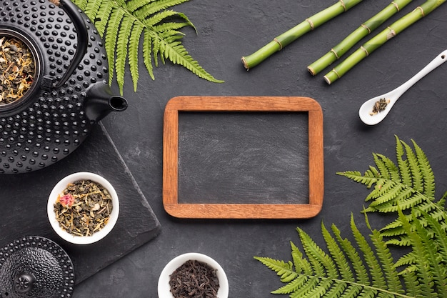 Ziołowej herbaty składnik z pustym łupkiem na czarnym textured tle