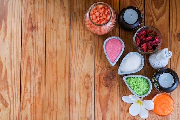 Ziołowy kompres i sól, masują produkty dla zdrowia na drewnianym stołowym tle z copyspace