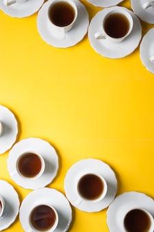 Ziołowy kubek herbaty i spodki na rogu żółtego tła