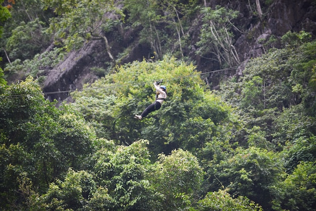 Zipline ekscytująca aktywność sportowa wisi na dużym drzewie w lesie w vang vieng laos