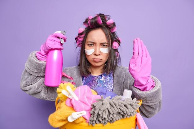 Zirytowana azjatka wykonuje gest zatrzymania, prosząc o trzymanie, zakazuje działania, ubrana w domowy szlafrok, gumowe rękawiczki, zajęta czyszczeniem i praniem, układa fryzurę w pomieszczeniu. koncepcja sprzątania