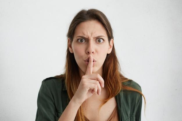 Zirytowana brunetka kobieta pokazując znak ciszy palcem wskazującym. ładna kobieta o dużych, ciemnych oczach marszczy brwi z niezadowoleniem, prosząc o ciszę w izolacji