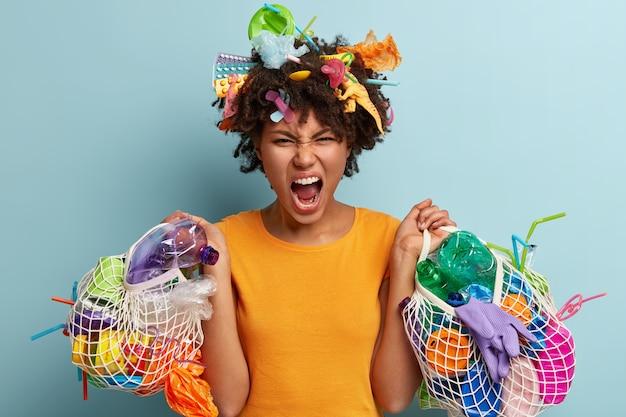Zirytowana czarna młoda kobieta zbiera plastikowe odpady, otwiera usta, trzyma siatkowe worki ze śmieciami, wyraża negatywne emocje, żąda ratowania przyrody, przetwarza śmieci. problem środowiska