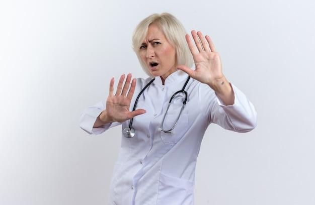 Zirytowana dorosła słowiańska lekarka w szacie medycznej ze stetoskopem stojąca z uniesionymi rękami na białym tle z kopią przestrzeni