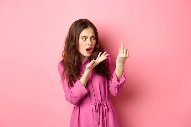 Zirytowana dziewczyna kłócąca się o oświadczyny, chce się ożenić, pokazuje palec bez pierścionka zaręczynowego, stoi zdezorientowana na różowej ścianie. koncepcja relacji