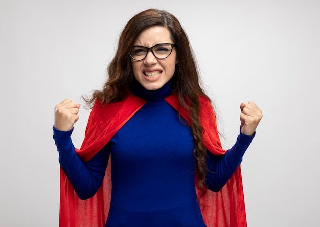 Zirytowana dziewczyna superbohatera kaukaskiego w czerwonej pelerynie w okularach optycznych trzyma pięści na biało