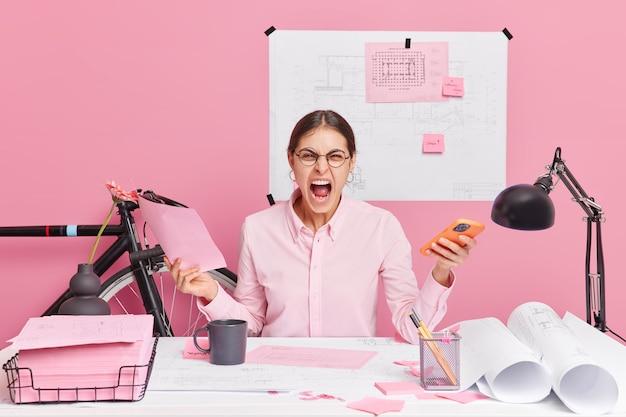 Zirytowana europejka krzyczy głośno trzymając telefon komórkowy, a papierowy dokument krzyczy ze złością pracuje nad szkicami ma dużo pracy siedzi przy biurku. koncepcja negatywnych emocji w pracy edukacyjnej