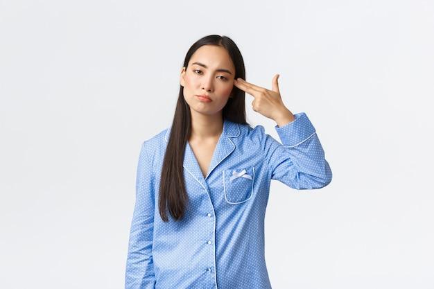 Zirytowana i zaniepokojona azjatka w niebieskiej piżamie patrząca niechętnie, strzelająca do siebie gestem pistoletu, jakby miała dosyć, zmęczona słyszeniem lub widzeniem czegoś nudnego lub głupiego, białe tło.