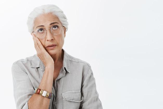Zirytowana i zaniepokojona starsza kobieta w okularach przewraca oczami i wzdycha ze zdziwieniem
