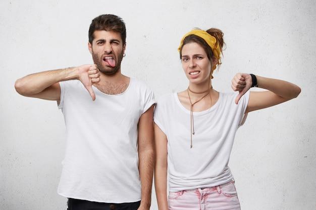 Zirytowana i zniesmaczona młoda europejska para w stylowych ubraniach wyrażająca niechęć, dezaprobatę, brak szacunku lub lekceważenie gestami, pokazaniem kciuków w dół i grymasem