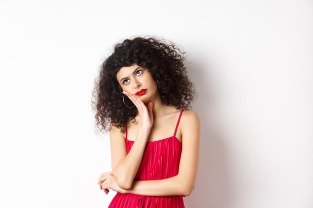 Zirytowana i znudzona młoda kobieta z kręconymi włosami, odwraca wzrok, zmartwiona, szczupła twarz na dłoni, stoi zaniepokojona w czerwonej sukience na białym tle.