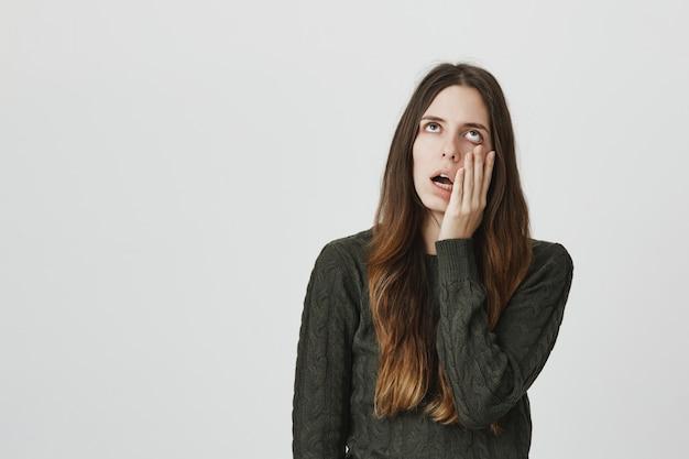 Zirytowana i zrozpaczona młoda kobieta przewraca oczami i zamiera na twarz
