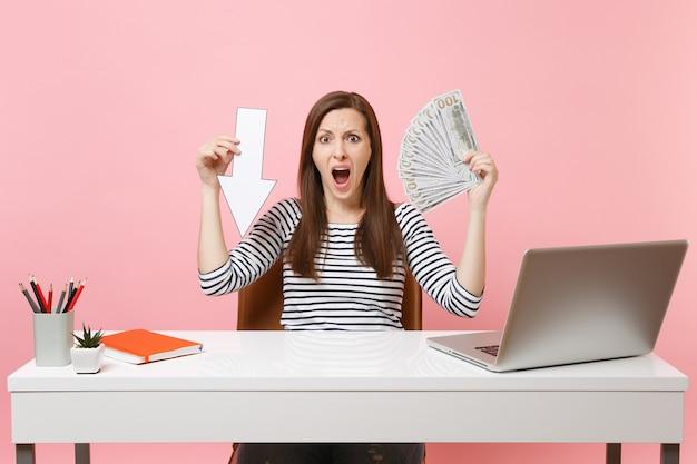 Zirytowana kobieta krzyczy, trzymając wciśniętą strzałkę spadku wartości, mnóstwo dolarów gotówki, praca przy białym biurku z laptopem na pc