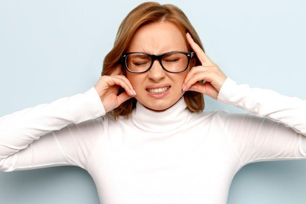 Zirytowana kobieta w okularach zamyka uszy, zamyka oczy, stara się zachować spokój i przejąć kontrolę nad emocjami, nie chcąc słyszeć