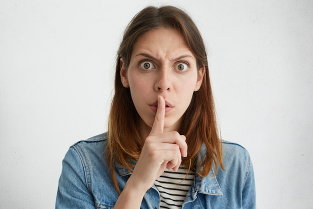 Zirytowana kobieta wpatrująca się ciemnymi oczami z palcem wskazującym na usta prosząca o ciszę.