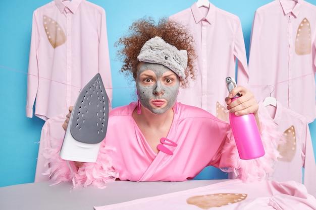 Zirytowana kobieta z kręconymi włosami wygląda na zdeterminowaną, trzyma butelkę z rozpylaczem i żelazko elektryczne, zajęta pracami domowymi, nosi domowe ubrania pozuje na niebieskiej ścianie z koszulami wiszącymi z tyłu
