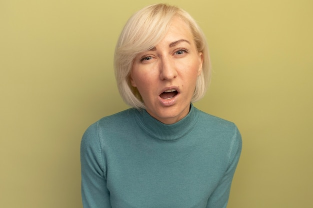 Zirytowana ładna blondynka słowiańska kobieta patrzy z przodu na białym tle na oliwkowej ścianie