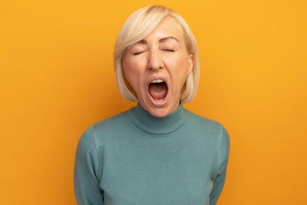 Zirytowana ładna blondynka słowiańska kobieta stoi z zamkniętymi oczami, krzycząc na kogoś odizolowanego na pomarańczowej ścianie