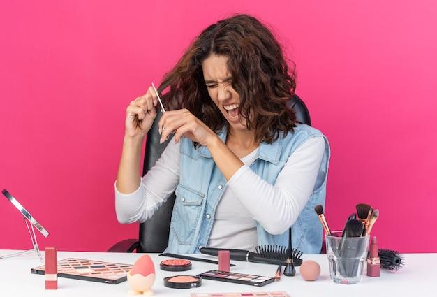 Zirytowana ładna kaukaska kobieta siedzi przy stole z narzędziami do makijażu, tnąc jej włosy nożyczkami na różowej ścianie z kopią przestrzeni