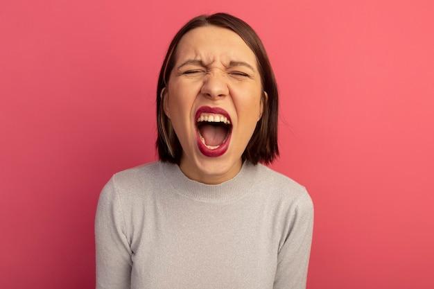 Zirytowana ładna kobieta krzyczy na białym tle na różowej ścianie