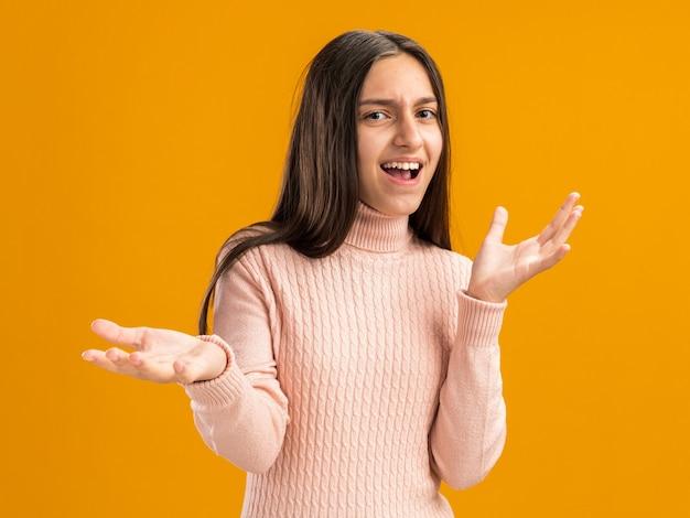 Zirytowana ładna nastolatka pokazująca puste ręce izolowane na pomarańczowej ścianie