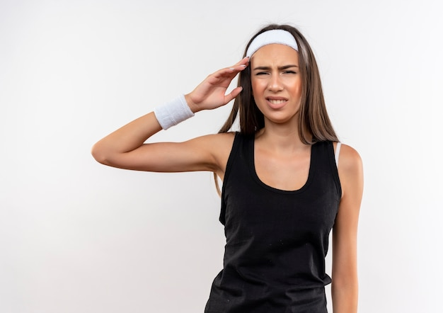 Zirytowana ładna wysportowana dziewczyna nosząca opaskę na głowę i nadgarstek, kładąca rękę w pobliżu głowy odizolowaną na białej ścianie
