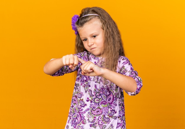 Zirytowana mała blondynka kładzie palec na dłoni i wygląda na odizolowaną na pomarańczowej ścianie z miejscem na kopię