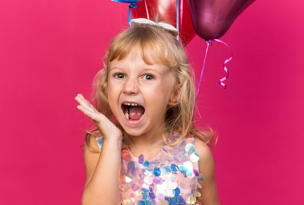 Zirytowana mała blondynka stojąca z balonami helowymi na białym tle na różowej ścianie z miejsca na kopię