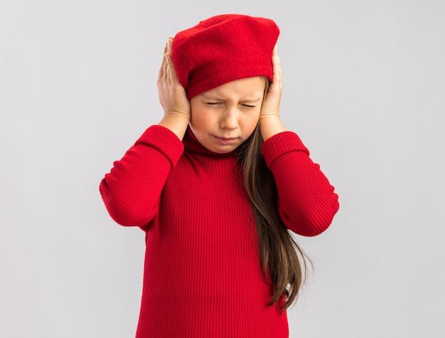 Zirytowana mała blondynka w czerwonym berecie trzymająca ręce na głowie z zamkniętymi oczami na białym tle na białej ścianie z miejscem na kopię