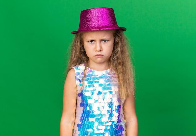 Zirytowana mała blondynka w fioletowym kapeluszu imprezowym wygląda na odizolowaną na zielonej ścianie z miejscem na kopię