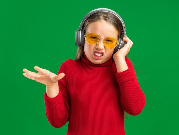 Zirytowana mała blondynka w słuchawkach, chwytająca słuchawki i trzymająca rękę w powietrzu, odizolowana na zielonej ścianie z miejscem na kopię