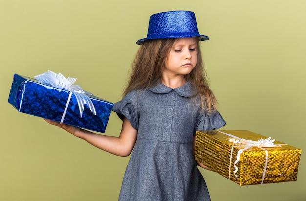 Zirytowana mała blondynka z niebieską czapką, trzymając i patrząc na pudełka na prezenty odizolowane na oliwkowej ścianie z miejsca na kopię