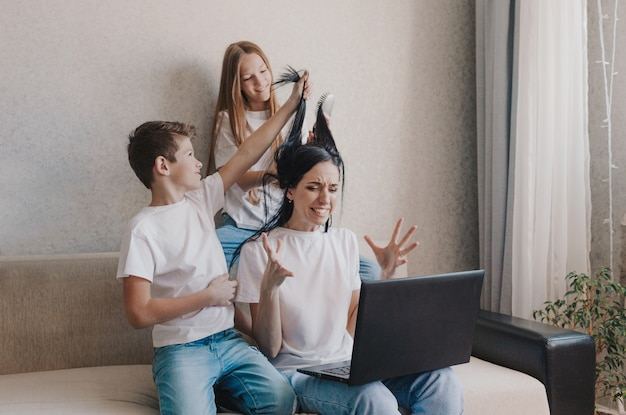 Zirytowana mama siada na kanapie i pracuje w domu na laptopie, aktywne dzieci bawią się włosami mamy, uczesują
