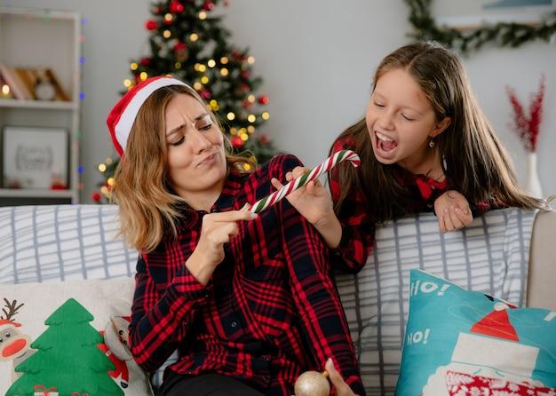 Zirytowana matka w czapce mikołaja próbuje zabrać córkę z cukierkiem, siedząc na kanapie i ciesząc się świątecznymi chwilami w domu