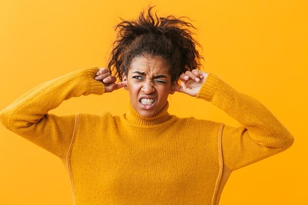 Zirytowana Młoda Afrykańska Kobieta Ubrana W Sweter Stojący Na Białym Tle, Zakrywaj Uszy Premium Zdjęcia