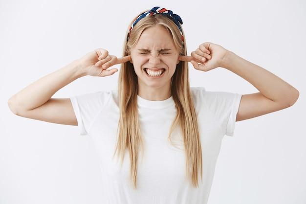 Zirytowana młoda blond dziewczyna pozuje przy białej ścianie