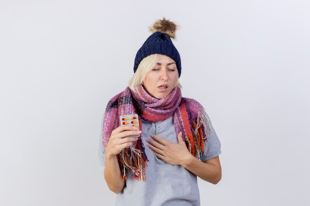 Zirytowana młoda blondynka chora kobieta w czapce zimowej i szaliku kładzie rękę na klatce piersiowej i trzyma paczkę tabletek medycznych na białej ścianie