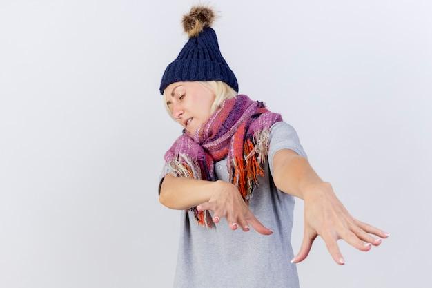 Zirytowana młoda blondynka chora kobieta w czapce zimowej i szaliku wyciągając ręce na białym tle na białej ścianie