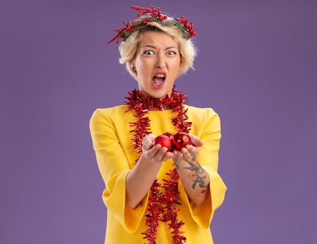 Zirytowana młoda blondynka ubrana w świąteczny wieniec na głowę i świecącą girlandę wokół szyi, patrząc wyciągając świąteczne bombki odizolowane na fioletowej ścianie z miejscem na kopię