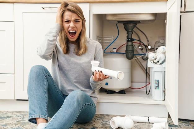 Zirytowana młoda blondynka z rurami kanalizacyjnymi krzyczącą siedząc na podłodze w pobliżu zlewu kuchennego