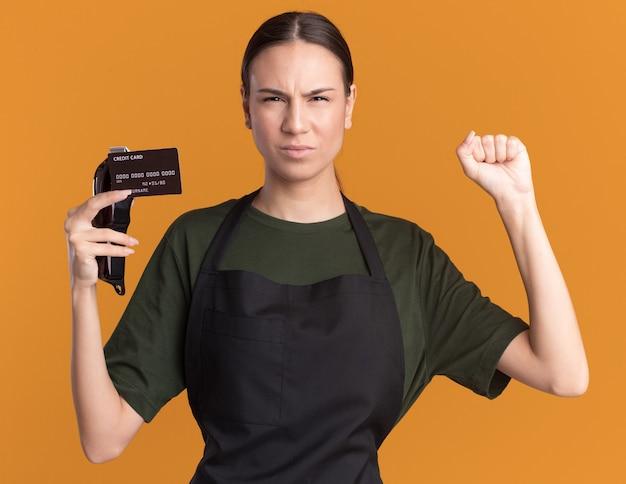 Zirytowana młoda brunetka fryzjer dziewczyna w mundurze trzyma pięść w górze trzyma maszynkę do strzyżenia włosów i kartę kredytową na pomarańczowo